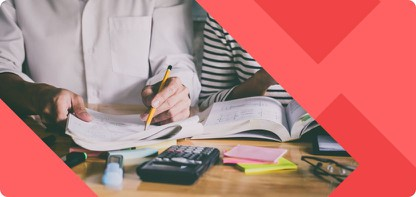 Junger Mann sitzt an einem Schreibtisch auf dem Notizzettel und Taschenrechner liegen und notiert etwas mit Bleistift in ein Heft