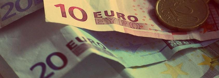 Geldscheine und Münzen liegen auf dem Tisch